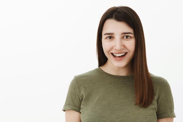 Zorgeloze, vrolijke en optimistische jonge brunette van in de 20 draagt een olijfgroen t-shirt breed glimlachend van verbazing en vreugde, plezier maken, zich vrolijk voelen en vermaakt als geamuseerd over de grijze muur