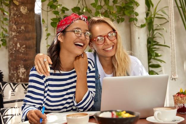Zorgeloze vrolijke jongeren omhelzen elkaar, hebben een vriendschappelijke relatie, lachen vrolijk, kijken naar interessante programma's op internet