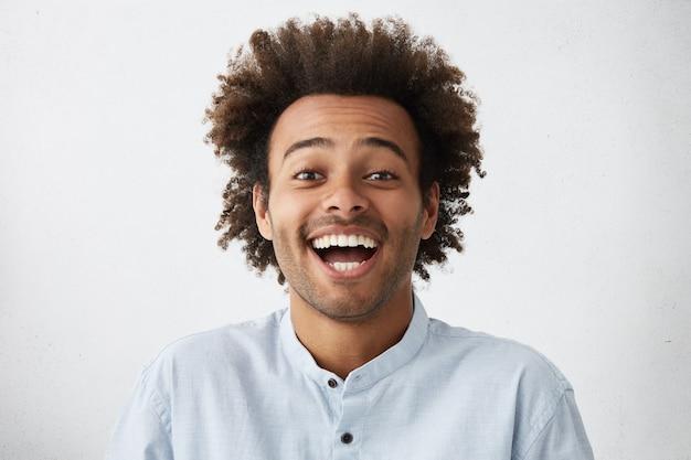 Zorgeloze vrolijke knappe afro-amerikaanse man met borstelige kapsel