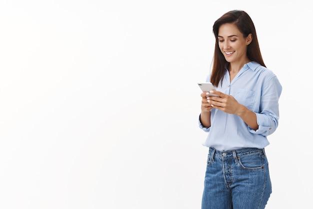 Zorgeloze vrolijke vrouwelijke ondernemer wacht afhaalkoffie, bestel lunch online app, glimlach verrukt, houd smartphone vast, lees sms-telefoonscherm, sta vrolijk op de witte muur