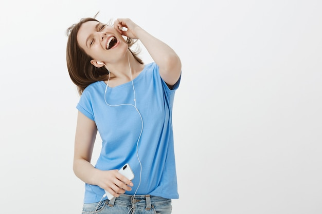 Zorgeloze vrouw dansen en zingen, muziek luisteren via koptelefoon op mobiele telefoon
