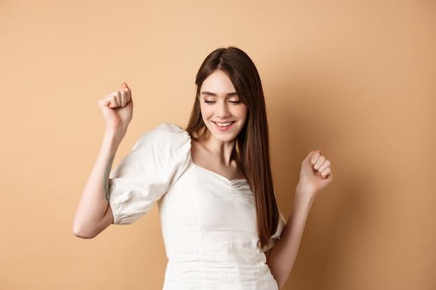 Zorgeloze vrouw die danst en plezier heeft, sluit de ogen en lacht terwijl ze op een beige achtergrond staat