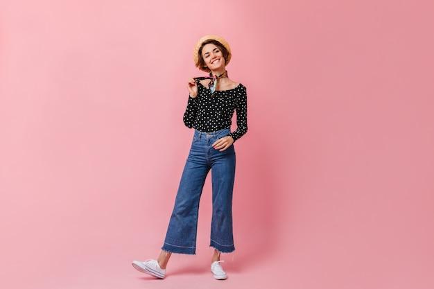 Zorgeloze vrouw die in vintage jeans voorzijde bekijkt