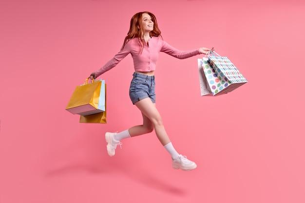 Zorgeloze vrouw die zich verheugt over verkooptijd die op roze studioachtergrond wordt geïsoleerd die vrijetijdskleding draagt.