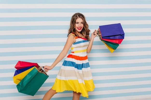 Zorgeloze vrouw in zomerjurk genieten van winkelen. schitterend wit meisje met kleurrijke tassen uit haar favoriete winkel.