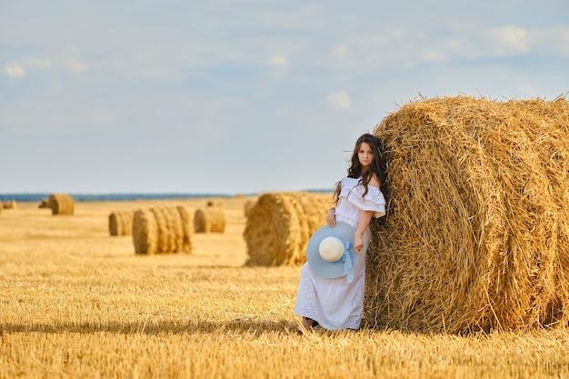 Zorgeloze vrouw leunend naar een enorme strohalm op het veld in een zonnige dag