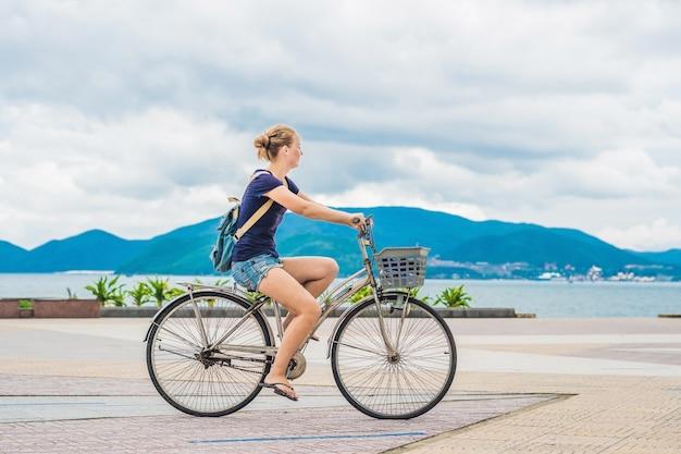 Zorgeloze vrouw met fietsen door de zee met plezier en lachend.
