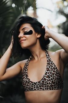 Zorgeloze vrouw met gebruinde huid die van vakantie geniet. buiten schot van charmante vrouw met ooglapjes op natuur achtergrond.