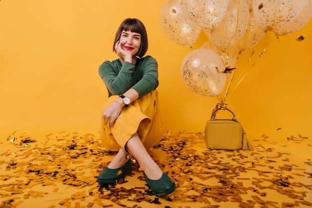 Zorgeloze vrouw met kort kapsel zitten met een zachte glimlach. indoor portret van innemend meisje omringd door confetti en feestballonnen.