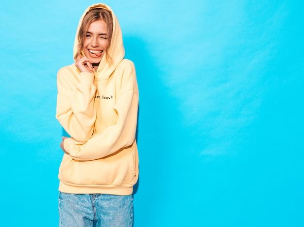 Zorgeloze vrouw poseren in de buurt van blauwe muur in de studio. positief model met plezier, toont tong en knipoogt
