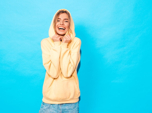Zorgeloze vrouw poseren in de buurt van blauwe muur in de studio. positief model met plezier