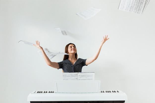Zorgeloze vrouwelijke pianospeler die de muzikale bladen in de lucht werpen tegen witte achtergrond
