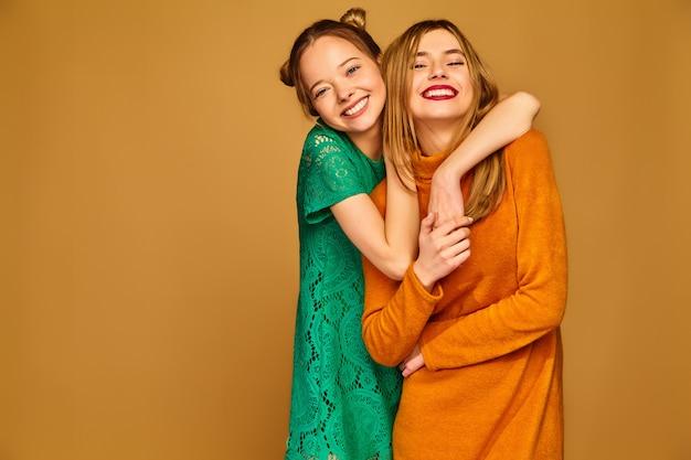 Zorgeloze vrouwen geïsoleerd op gouden muur positieve modellen poseren met hun jurken