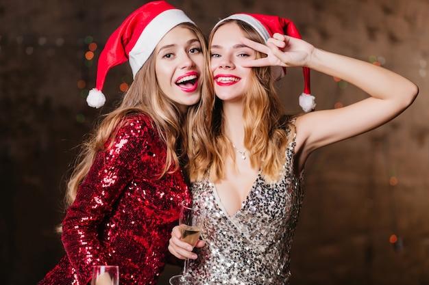Zorgeloze vrouwen in nieuwe jaar hoeden grappig dansen en lachen, tijd doorbrengen op feestje