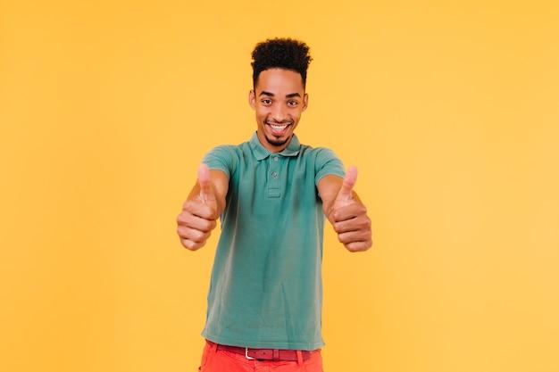 Zorgeloze zwarte man in casual groen t-shirt glimlachen. indoor foto van emotionele afrikaanse man poseren met duimen omhoog.