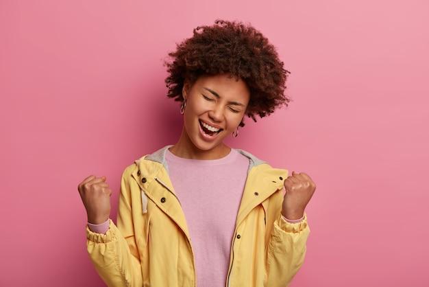 Zorgeloze zwarte vrouw balt vuisten van vreugde, kantelt het hoofd en voelt zich als winnaar, viert de overwinning, sluit de ogen met plezier, draagt casual trui en jas