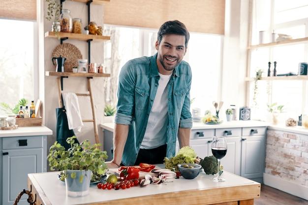 Zorgen voor zijn gezondheid. knappe jongeman in vrijetijdskleding die naar de camera kijkt en glimlacht terwijl hij thuis in de keuken staat