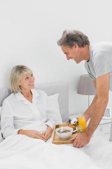 Zorgvuldig breng de mens ontbijt in bed aan zijn partner