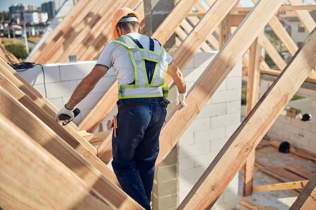 Zorgvuldige mannelijke bouwer die een boor vasthoudt en op een dak van een nieuw gebouw loopt