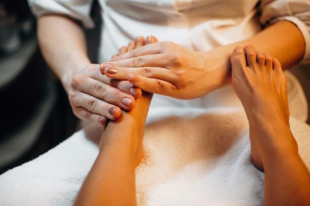 Zorgvuldige spa-medewerker masseert de voeten van de klant voordat hij naar de volgende spa-procedure gaat