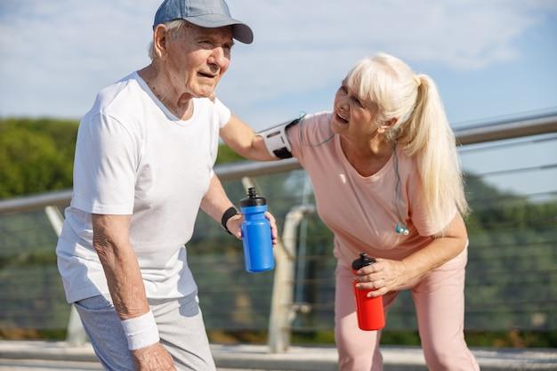 Zorgvuldige volwassen vrouw zorgt voor vermoeide man tijdens training op footbridg
