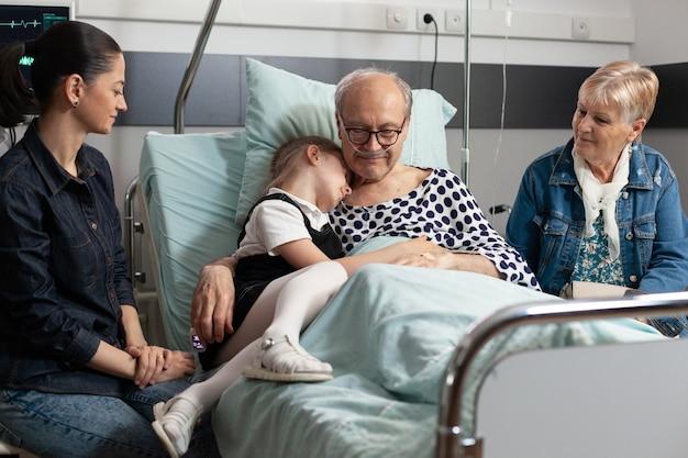 Zorgzaam kleinkind knuffelt zieke bejaarde grootouder die liefde toont