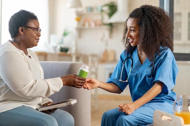 Zorgzaam medisch begeleider. dankbare bejaarde vrouw die pillen slikt van zorgzame medische begeleider in het verpleeghuis