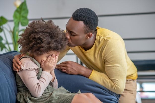 Zorgzaam, vader. jonge, donkere, zorgzame vader kalmeert een verdrietig dochtertje dat haar gezicht bedekt met handen zittend op de bank