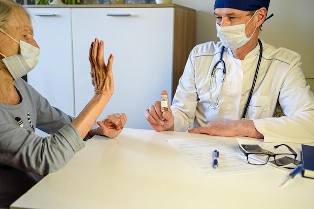 Zorgzame arts helpt een negatieve bejaarde grootmoeder van 85 jaar - een patiënt thuis of in het ziekenhuis.
