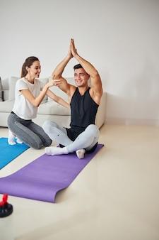 Zorgzame brunette vrouw helpt haar vriendje yoga te doen