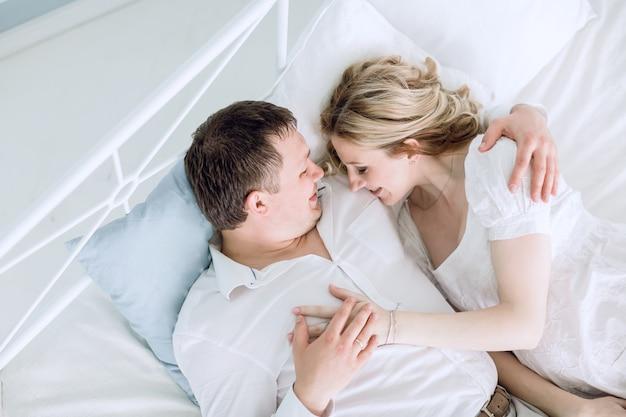 Zorgzame echtgenoot en zijn zwangere vrouw die op het bed liggen