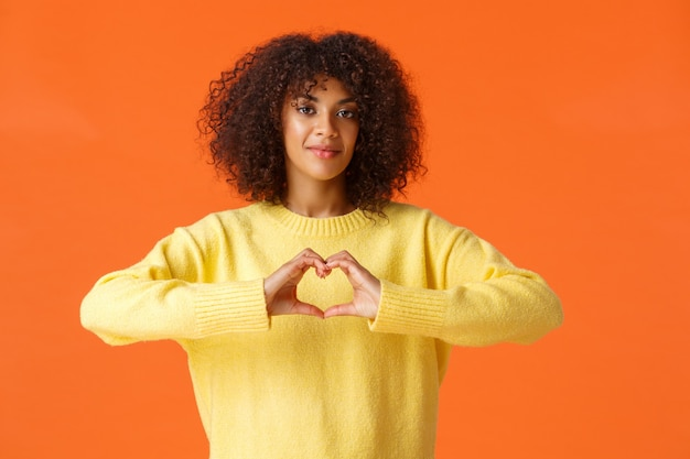 Zorgzame en tedere, mooie romantische afro-amerikaanse vrouw uit haar gevoelens, toont hartgebaar, belijdt liefde op valentijnsdag, staande oranje muur blij.