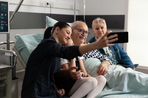 Zorgzame familie die selfie neemt met zieke bejaarde grootvader met behulp van moderne smartphone
