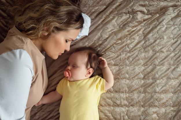 Zorgzame jonge moeder ligt op groot bed in de buurt van babymeisje