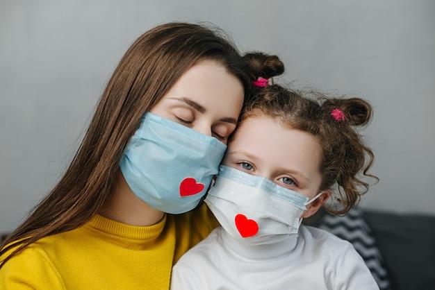 Zorgzame jonge moeder omhelst kleine schattige kinddochter met een medisch gezichtsmasker en een rood hart erop om waardering te tonen en alle essentiële medewerkers te bedanken tijdens de covid-19-pandemie