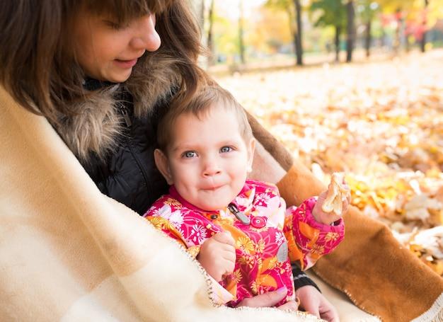 Zorgzame jonge mooie moeder sluit met een deken van zichzelf en haar kleine vrolijke kind tijdens het wandelen in het herfstpark. concept van gezellige picknickwandeling in de herfsttijd