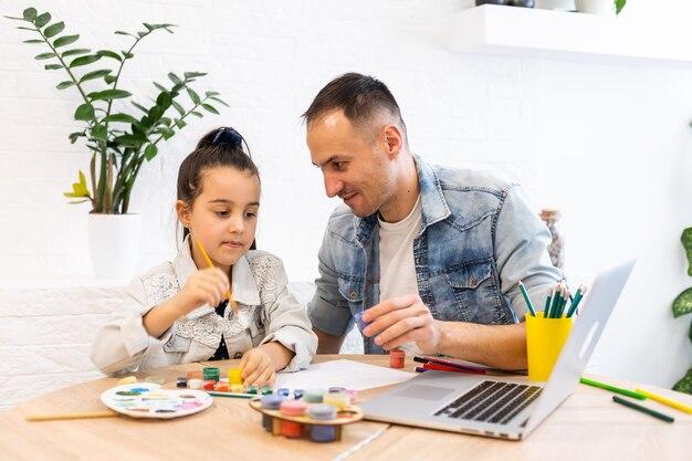 Zorgzame jonge vader helpt kleuter dochter samen studeren kijken online les op laptop