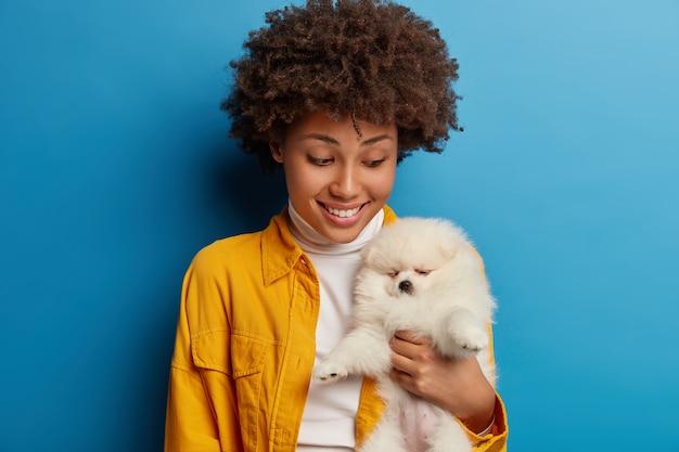 Zorgzame jonge vrouw kijkt met geluk naar slapende miniatuur pluizige hond, blij om een dier als cadeau te krijgen