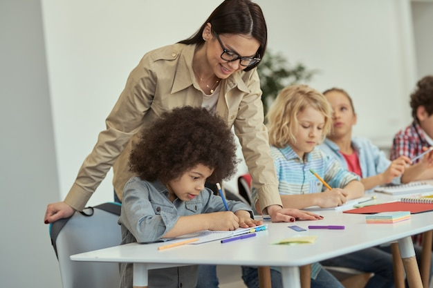 Zorgzame jonge vrouwelijke leraar met een bril die kleine schooljongens helpt die aan tafel zitten te studeren
