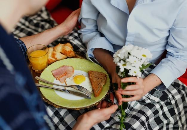 Zorgzame man bracht ontbijt met eieren, spek, toast en sinaasappelsap, bloemen in het bed van zijn vriendin, die bedekt is met plaid