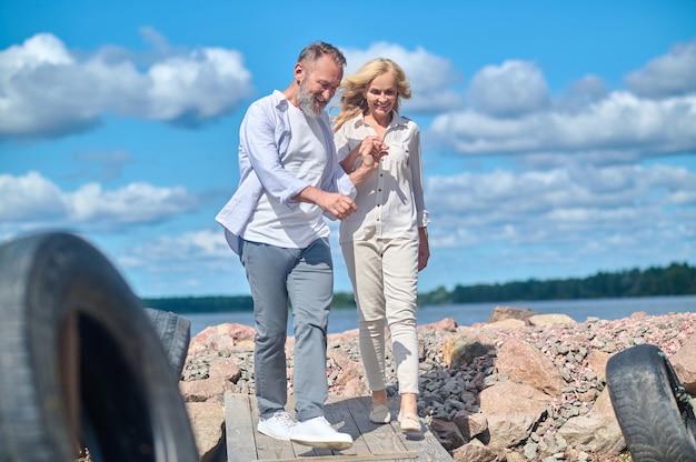Zorgzame man en lachende vrouw op wandeling in de natuur