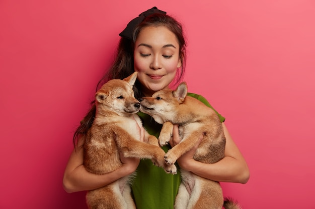 Zorgzame medelevende vrouwelijke vrijwilliger vond twee puppy's, draagt honden naar de schuilplaats, geeft gedragstraining aan huisdieren, poseert tegen een roze achtergrond.
