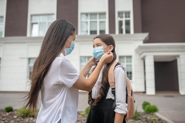 Zorgzame moeder beschermend masker voor haar dochter schoolmeisje permanent in schoolplein te zetten