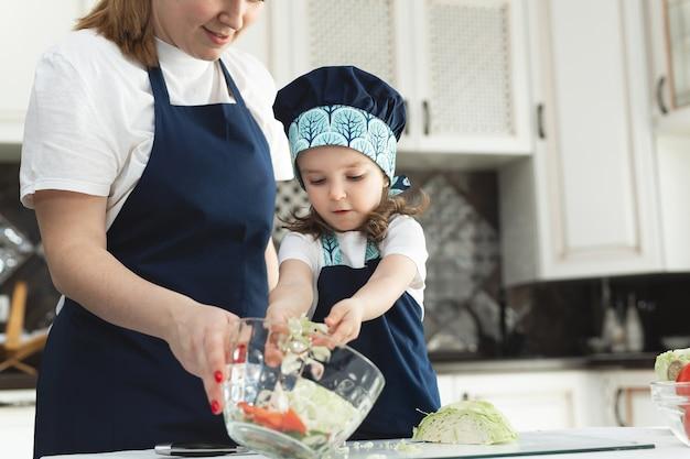 Zorgzame moeder die dochtertje leert om salade in de keuken te koken