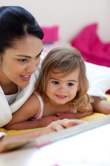 Zorgzame moeder die een boek met haar meisje leest