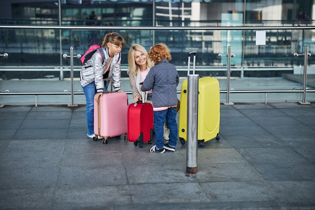 Zorgzame moeder die haar jongen hulp biedt met bagage