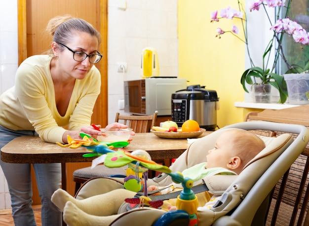 Zorgzame moeder geeft haar zes maanden oude zoon te eten