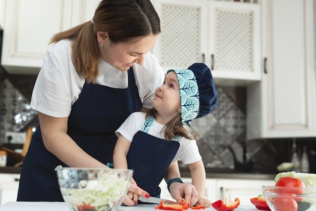 Zorgzame moeder leert haar dochtertje hoe ze een salade moet bereiden in de keuken, een jonge moeder en een charmant lief meisje kijken elkaar aan en glimlachen.