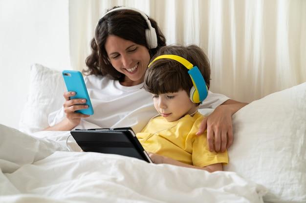 Zorgzame moeder succesvolle smm-manager netwerken in smartphone helpen zoontje met onderwijs op afstand