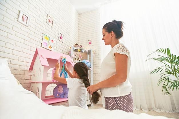 Zorgzame moeder vlecht het haar van haar dochter wanneer het meisje met speelgoed speelt
